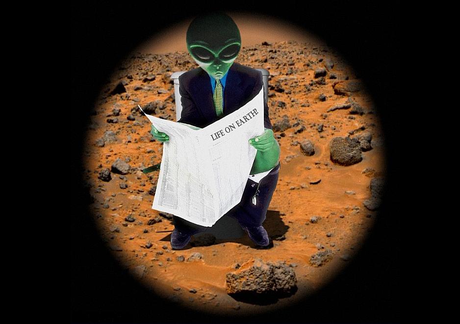 Alien leyendo el periodico
